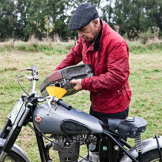 Jean-Yves Sellin remplit le réservoir de sa BBSA Goldstar 500 cc - Histoire veste Les Motocyclettistes