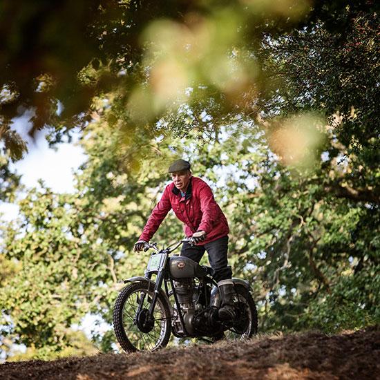 Jean-Yves Sellin debout sur sa BSA Goldstar 500 cc en haut d'une pente - Histoire veste Les Motocyclettistes