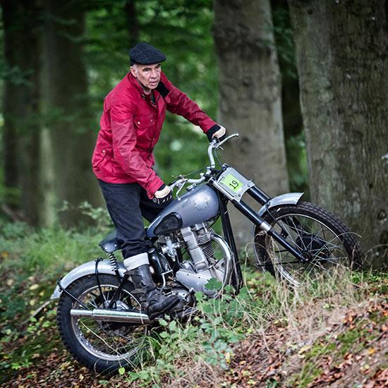 Jean-Yves Sellin dans les bois debout sur sa BSA Goldstar 500 cc - Histoire veste Les Motocyclettistes