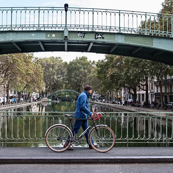 Redouane Rabahi marche sur un pont avec sa randonneuse CDF de 1948 - Histoire veste Galibier Les Motocyclettistes