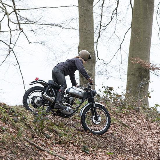 Zoé David debout sur sa BSA C15 T Usine de 1964 dans les bois - Histoire veste de femme 1962 Les Motocyclettistes